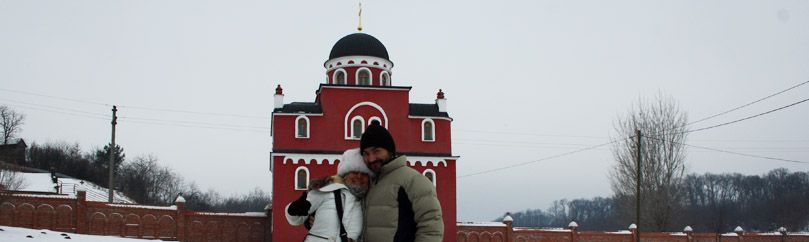 Couple in love is standing in front of the Krusedol monastery in Fruska gora in Serbia