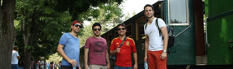 Group of four friends is standing beside the Sargan eight train on Mokra gora in Serbia