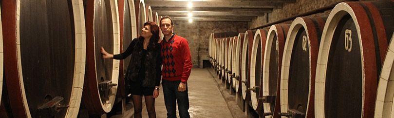 Married couple is standing between wine barrels of Royal wine cellar in Oplenac in Serbia
