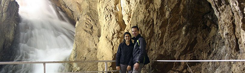 Married couple is posing beside the waterfall in Stopica cave on Zlatibor in Serbia