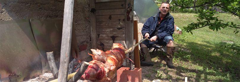 Man is roasting a pork.