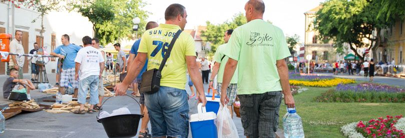 Two guys in yellow and green shirt are taking fishpot and other ingredients for fish stew in Sombor