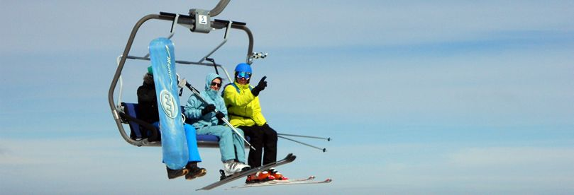 Three skiers on ski lift at Kopaonik ski resort
