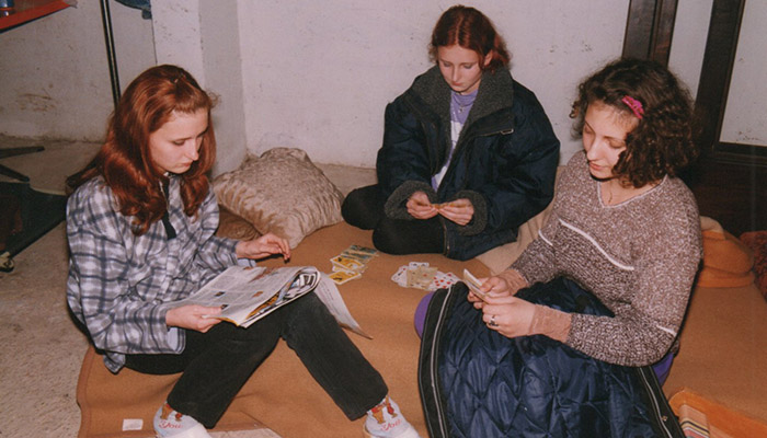 Three girls are playing cards in the basement during the NATO bombing of Serbia.
