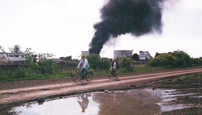 Two people are riding bikes, and behind them you can see the consequences of NATO bombing of Serbia.