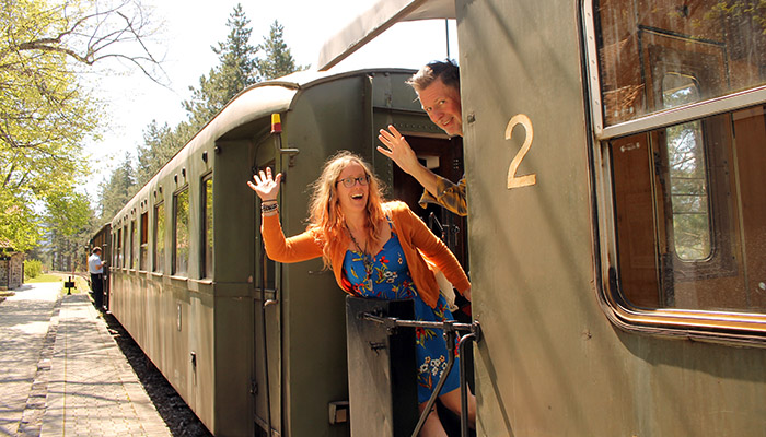 Couple is waving from Sargan Eight train as one of the Serbian top five destinations.