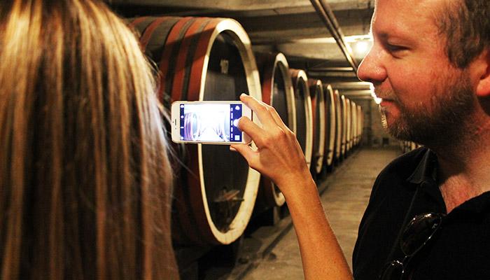Momak i devojka fotografišu vinski podrum u Kraljevoj vinariji.
