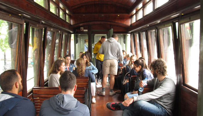 Young people are enjoying in old wagon with wooden seats and Sargan Eight train ride.