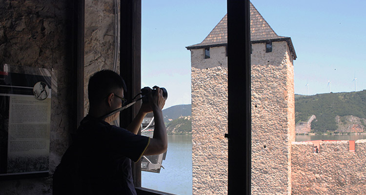 Guy is taking a photo of tower of Golubac fortress.